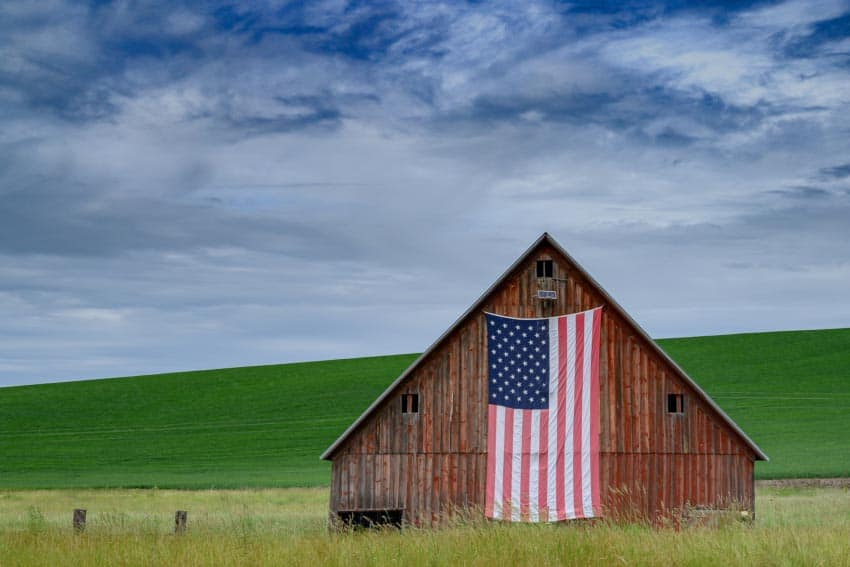 The Horn School red gable barn is adorned with the American flag.