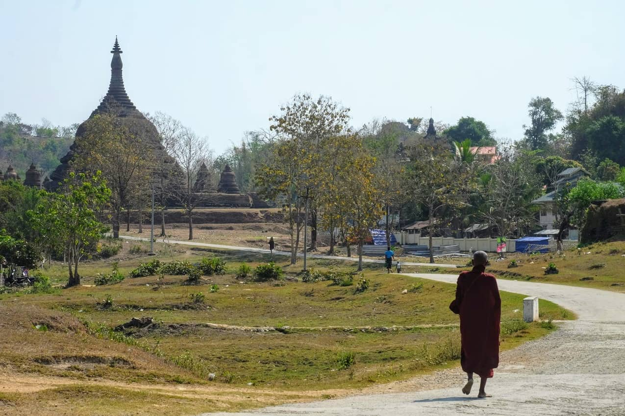 A monk wanders past the northern temples with faint gunfire in the background