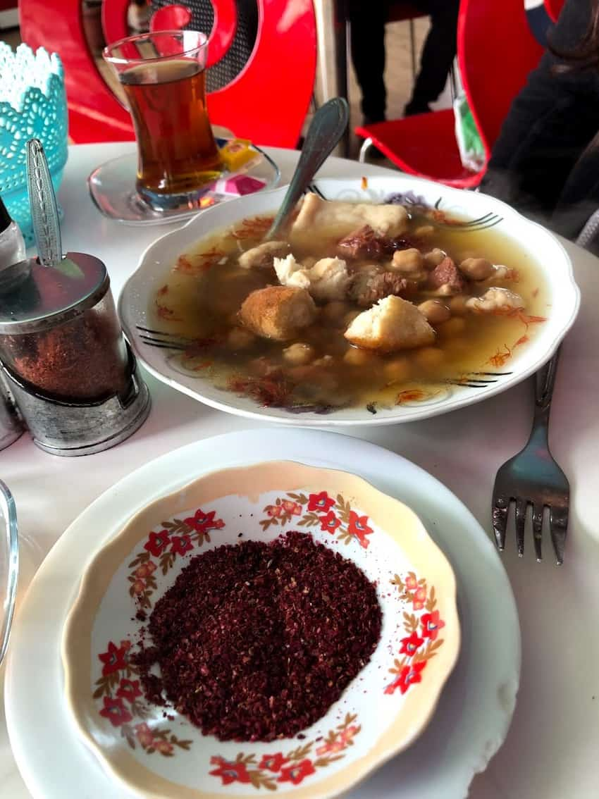 The famous Sheki Piti dish served with a side of spices and bread.