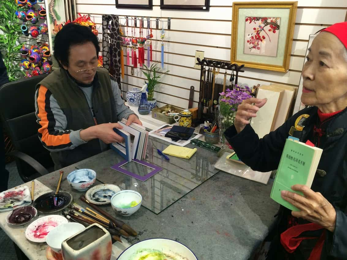Luo Wen Jing shows us his calligraphy skills in his Chinatown shop.