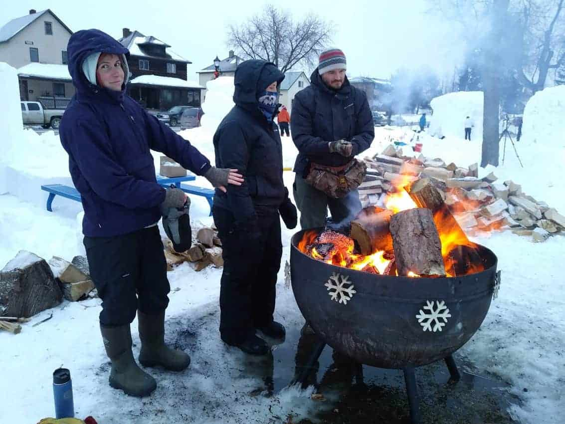 Snowcarvers warm their hands during Ely Winter Festival