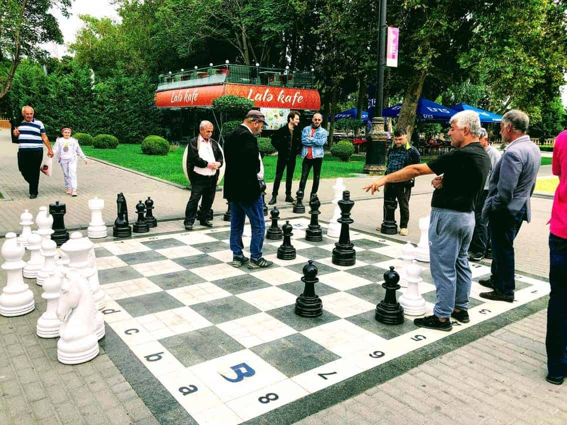 Locals play life-size chess on the Baku promenade near the Caspian Sea and Old City.