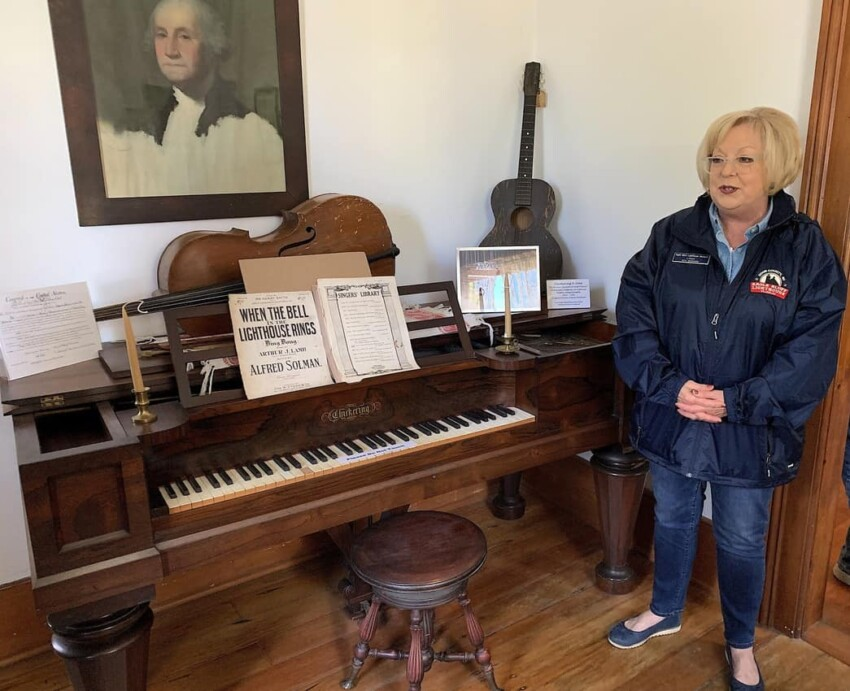 Linda Faust stands by the Rosewood piano used by the Duclon brothers in their family band.