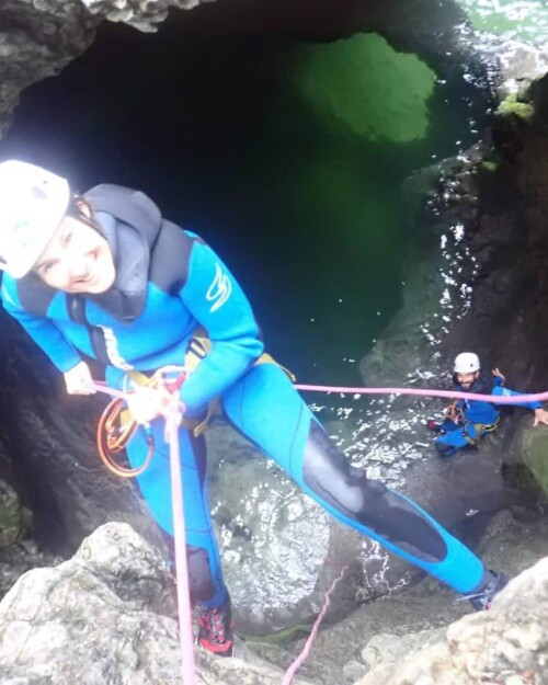 smiling while abseiling into canyon