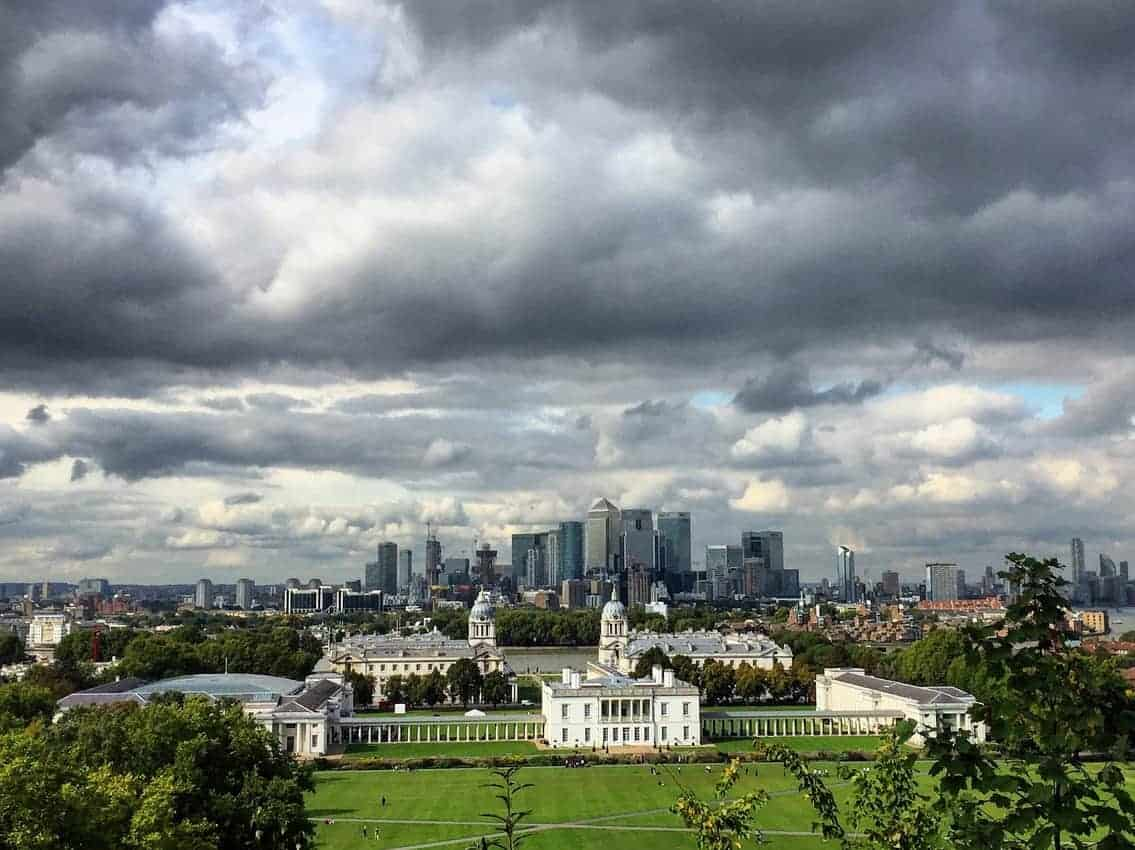 The National Maritime Museum in Greenwich, England with London skyline in the background. The photo is taken from the Greenwich Mean Time Observatory which shares the park with the Maritime Museum