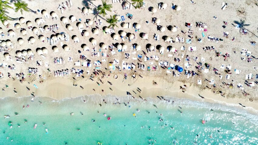 Beachgoers crowd the blissful white sand in Waikiki, finding shade under umbrellas and cooling off in the crystal clear ocean. Randall Kaplan photo.