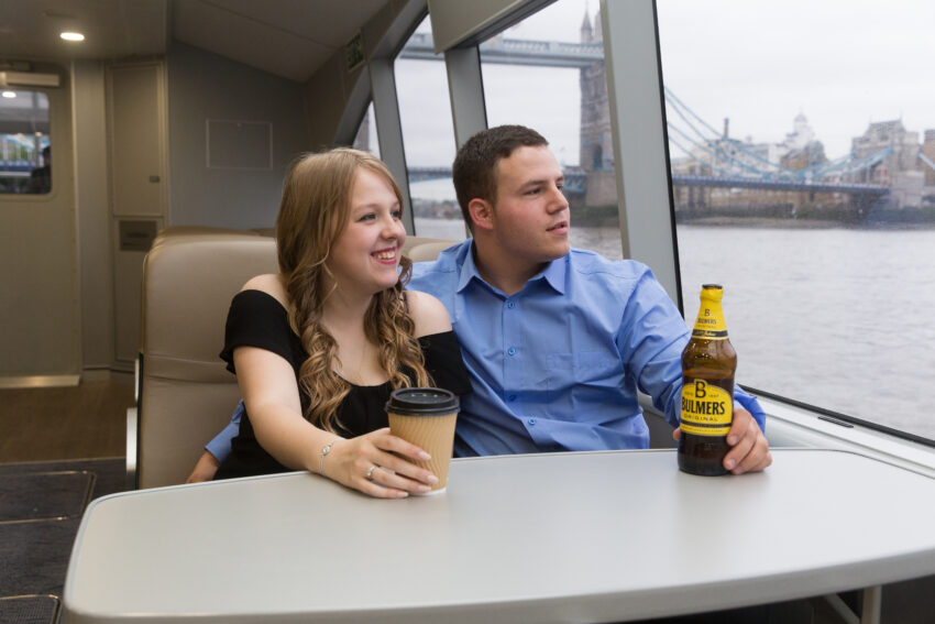 Couple enjoying drinks from the cafe. Uber Boat by Thames Clipper Photos.