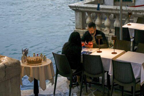 couple dining under a bridge in Venice