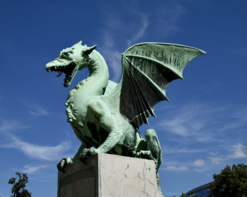 The famous Dragon Bridge has four large green dragons guarding it. Looking fierce with their tails wrapped around the entrance pillars. Ljubljana river