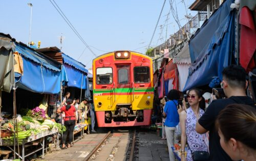 Don't be startled to see trains pass by the marketplace in Bangkok, Thailand.