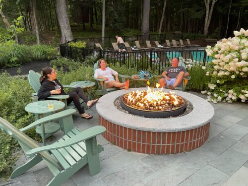 Guests enjoying the outdoor firepit near the pool at the Inn.