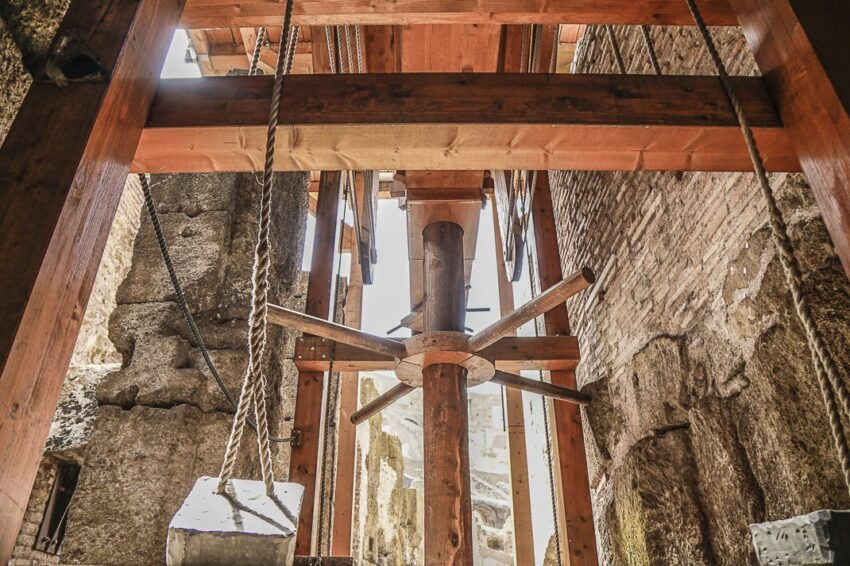 A replica elevator shows the wheel and counterweights that lift the animals to the Colosseum floor.