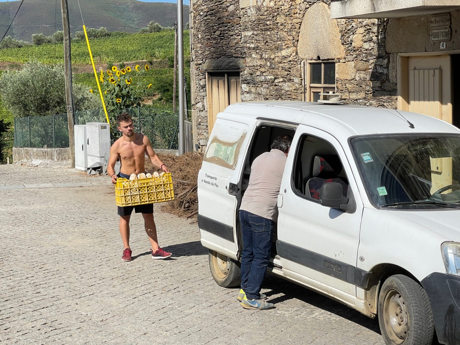 The baker's beefy assistant carries the day's loaves to the delivery van in Provesende, Portugal.