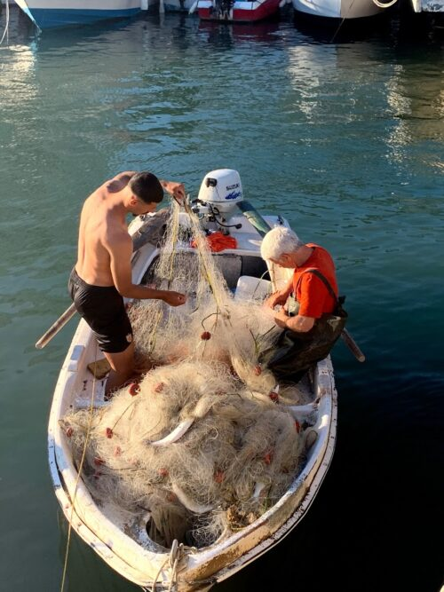 Father and son picking their catch out of their nets hitchhiking in Sarande Albania